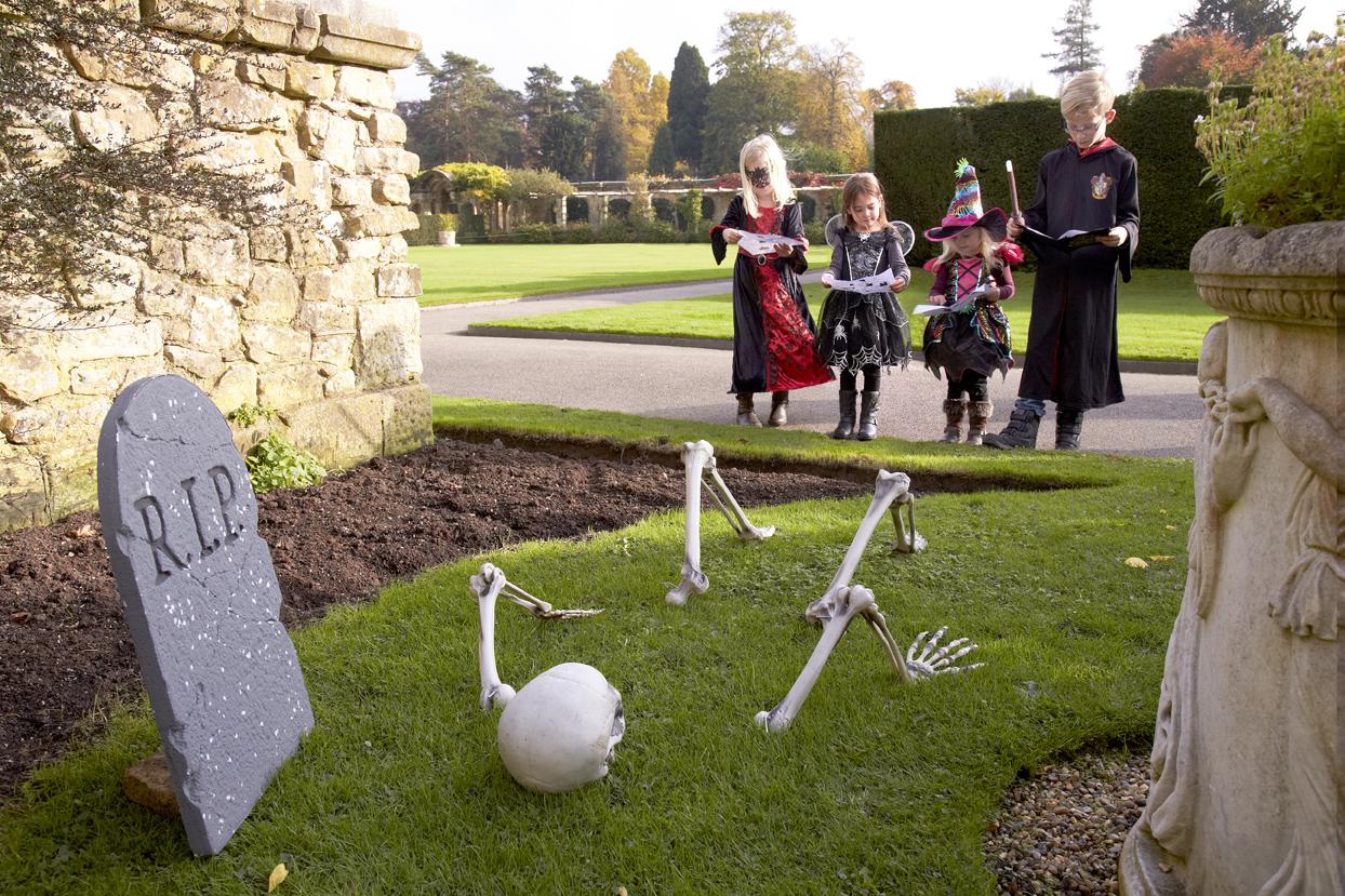 3 Children in Halloween costumes following a trail round Hever Castle Gardens, skeleton bones on grass