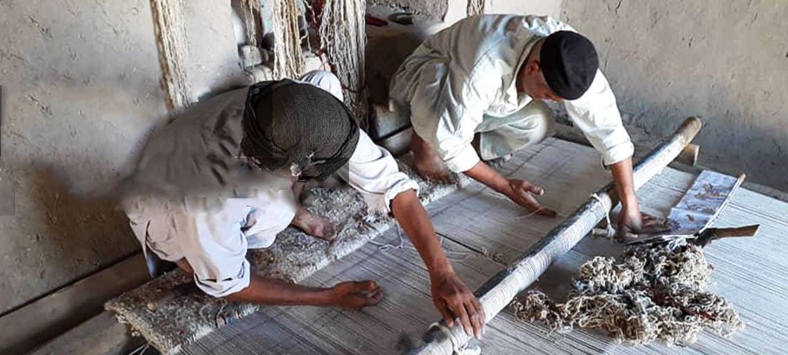 2 men working on a loom to create a rug - Oriental Rug Merchant, Royal Tunbridge Wells